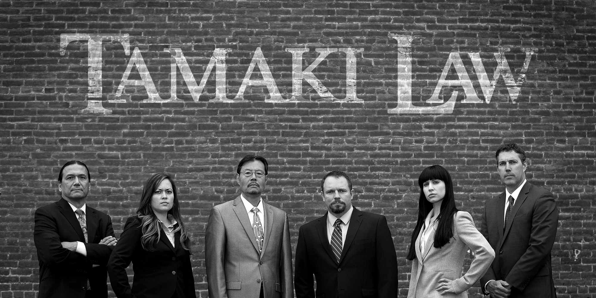Tamaki Law Team in front of a brick wall
